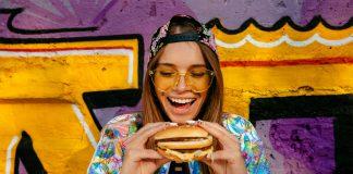 Junge Frau mit Burger in der Hand. © freepic.diller/Freepik