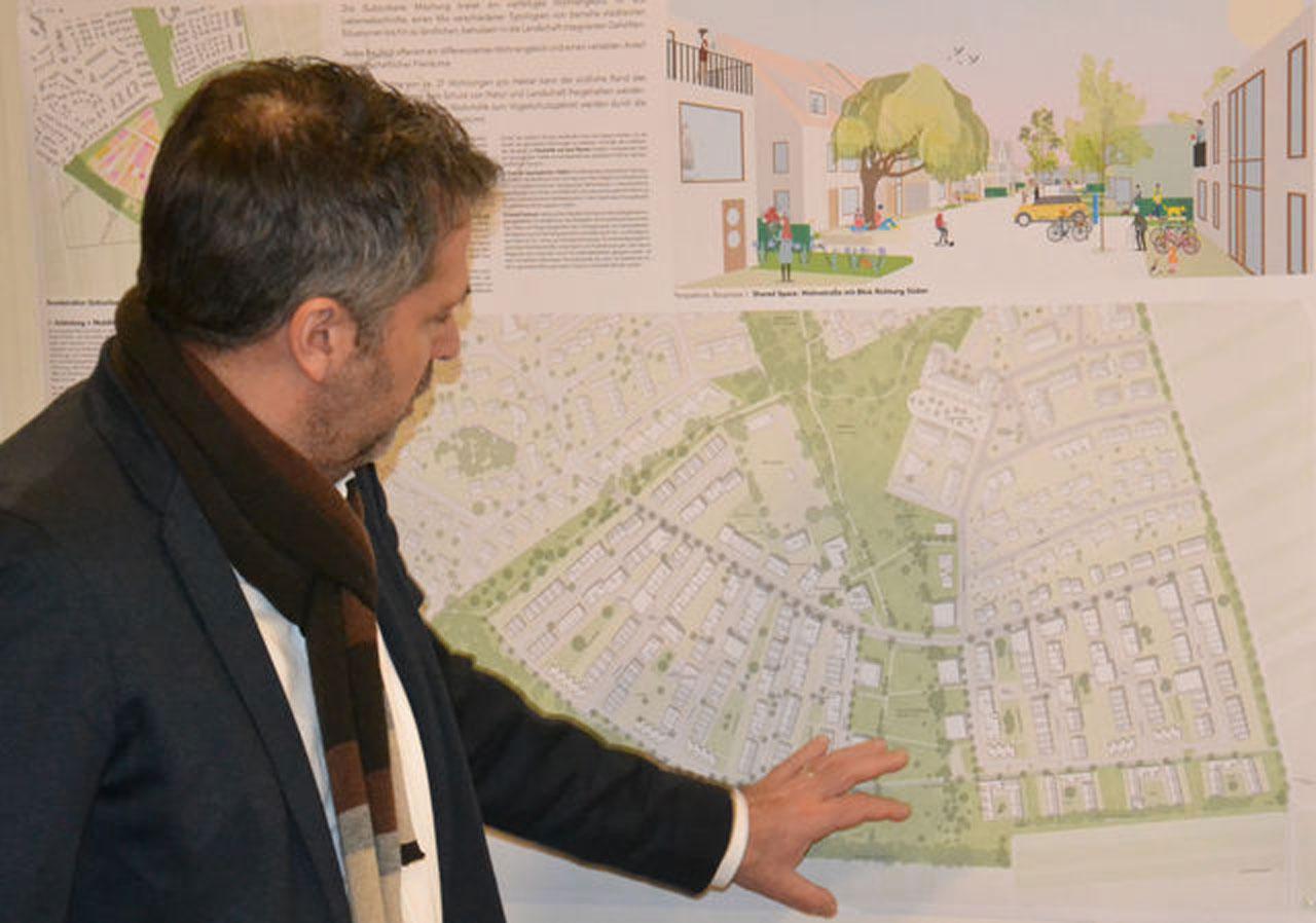 Preisrichter Torsten Becker erläutert die fächerförmige Struktur der Bebauung mit vielen Grünelementen aus dem Siegerentwurf. © Stadt Limburg